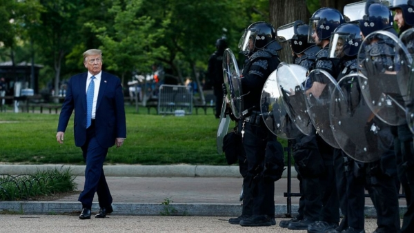 President Donald J. Trump walks past police in Lafayette Park after visiting outside St. John's Church across from the White House in Washington, DC, on Monday, June 1, 2020. Part of the church was set on fire during protests on Sunday night.
